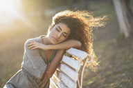 Portrait of young woman relaxing on bench in a park at sunset - JSMF00100