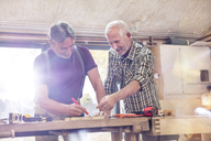 Male carpenters marking and measuring wood in workshop - CAIF07056