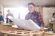 Portrait smiling male carpenter reviewing plans at wood boat in workshop - CAIF07065
