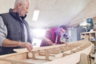 Male carpenters assembling wood boat in workshop - CAIF07071
