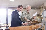 Male carpenter and customer examining wood kayak in workshop - CAIF07074