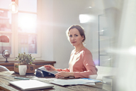 Portrait confident businesswoman using digital tablet at desk in office - CAIF07083