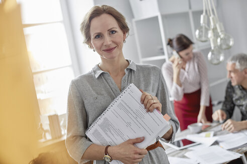 Portrait smiling businesswoman with paperwork in office meeting - CAIF07086