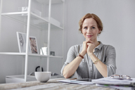Portrait smiling, confident businesswoman using digital tablet and drinking tea in office - CAIF07089