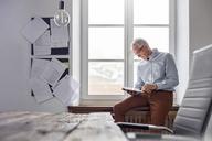 Businessman using digital tablet in office window - CAIF07098