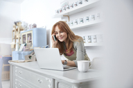 Smiling female business owner using laptop and talking on cell phone at counter in art paint shop - CAIF07137