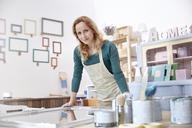 Portrait confident female artist painting mirror in art studio - CAIF07155