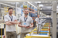 Portrait smiling, confident male workers with digital tablet on fiber optics factory floor - CAIF07182