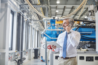 Male supervisor with digital tablet talking on cell phone next to plastic industrial molder machinery in factory - CAIF07206