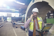 Male engineer with laptop talking on cell phone in steel factory - CAIF07257