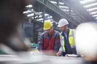 Male engineers using laptop in factory - CAIF07284