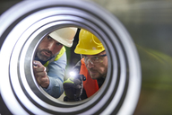 Serious male engineers with flashlights examining steel pipe - CAIF07323