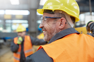 Profile smiling male worker in factory - CAIF07335