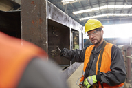 Male worker gesturing, explaining steel part to colleague in factory - CAIF07341