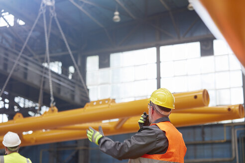 Male worker with walkie-talkie guiding lowering of equipment in factory - CAIF07347
