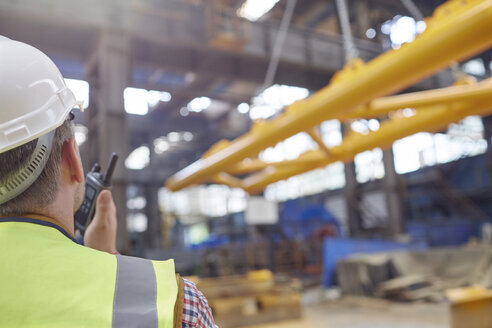 Male worker using walkie-talkie to guide hydraulic crane lowering equipment in factory - CAIF07362