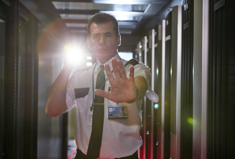 Portrait male security guard with flashlight gesturing stop in server room - CAIF07371