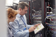 IT technicians with clipboard examining panel in server room - CAIF07380