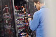 Male IT technician performing diagnostics on panel in server room - CAIF07386