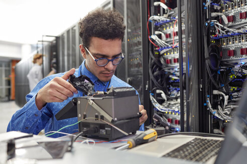 Male IT technician fixing equipment in server room - CAIF07410