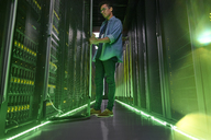 Male IT technician working in dark server room with glowing green panels - CAIF07419