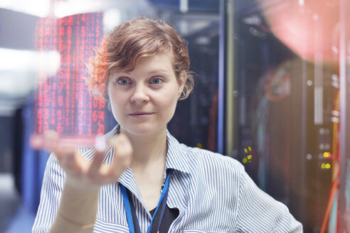 Female IT technician holding futuristic digital tablet in server room - CAIF07428
