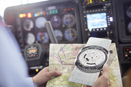 Pilot checking navigational map and compass instrument in airplane cockpit - CAIF07455