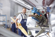 Portrait confident male engineer mechanic working on airplane in hangar - CAIF07461