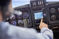 Male pilot using navigational instruments in airplane cockpit - CAIF07467
