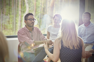 Attentive man listening to woman in group therapy session - CAIF07500