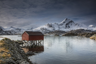 Snow covered mountains behind fishing hut over lake, Sund, Lofoten Islands, Norway - CAIF07516