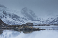 Snow covered craggy mountains over cold bay, Norway - CAIF07543
