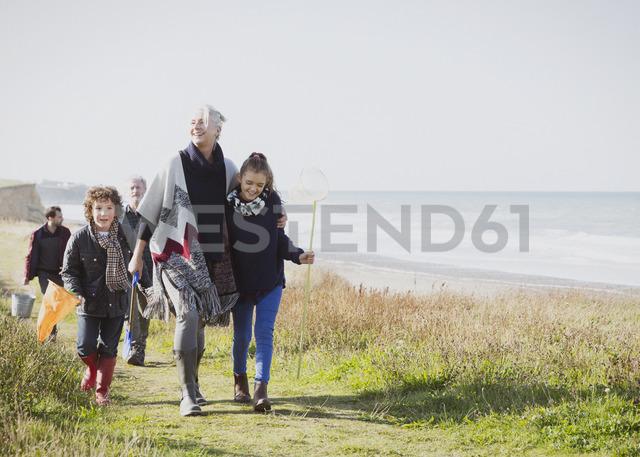 Multi-generation family walking on grassy beach path - CAIF07555
