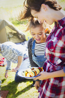 Mother and daughter with vegetable skewers at campsite - CAIF07564
