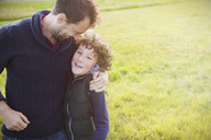 Father hugging son in field - CAIF07570