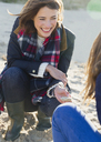 Smiling woman clamming on beach - CAIF07576