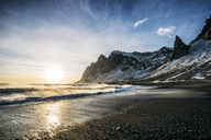 Sun setting over tranquil beach and snowy mountain, Iceland - CAIF07612