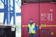 Worker smiling near cargo container - CAIF07657