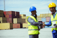 Worker and businessman shaking hands near cargo containers - CAIF07660