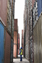 Worker standing between cargo containers - CAIF07669