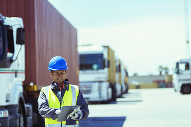 Worker using digital tablet near trucks with cargo containers - CAIF07672