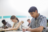 Students writing their GCSE examination in classroom - CAIF07690