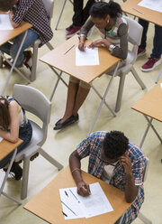 Elevated view of students writing their GCSE exam in classroom - CAIF07696