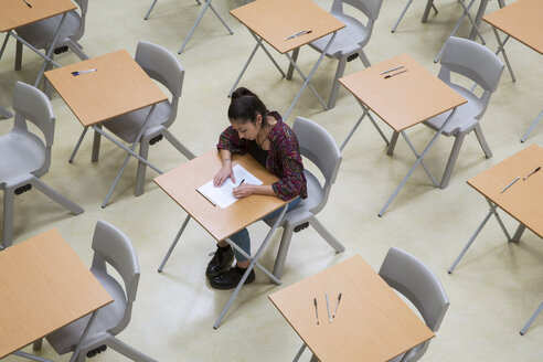 Elevated view of lone female student writing their GCSE exam in classroom - CAIF07702