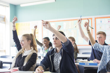 Students raising arms during lesson in classroom - CAIF07705