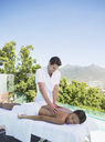 Woman receiving massage on spa patio - CAIF07720