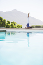 Woman practicing yoga at poolside - CAIF07738