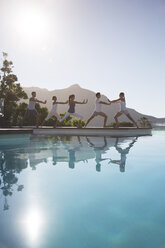 People practicing yoga at poolside - CAIF07741