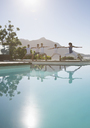 People practicing yoga at poolside - CAIF07744