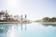 People practicing yoga at poolside - CAIF07750